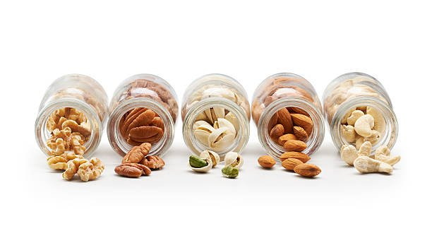 Picture of almonds, cashews, pistachios, walnuts and pecans in separate jars.