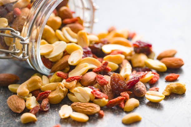 Picture of a mix of delicious nuts spilling out of a jar - it is difficult to separate the different nuts.